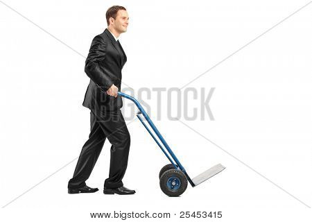 Smiling businessman pushing an empty handtruck isolated on white background