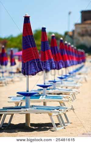 Sequence Of Parasols And Beech Chairs In Sicily