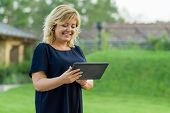 Outdoor Portrait Of Mature Business Woman With Digital Tablet, Background Green Garden Of A Private  poster