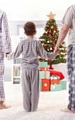 stock photo of nuclear family  - Family standing in pyjama holding hands on christmas morning - JPG