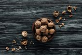 Walnuts In Wooden Bowl With Nutshells On Dark Wooden Table poster