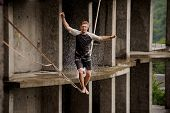 Young Brave Man Balancing On A Slackline Against The Background Of High Empty Building On Summer Day poster