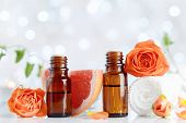 Essential Oil Bottles With Towel, Grapefruit And Rose Flowers On White Table. Spa, Aromatherapy, Wel poster
