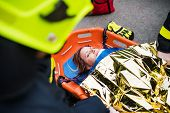 An Injured Woman In A Plastic Stretcher After A Car Accident, Covered By Thermal Blanket. poster