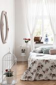 Real Photo Of Bright Bedroom Interior With Window With Curtains, Fresh Roses In Bird Cage, Bed With poster