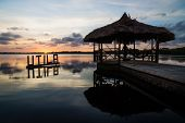 Sun Setting At The Calm Lagoon Behind Utila Sign And Dock, Utila, Honduras, Central America poster