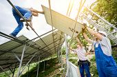 Stand-alone Solar Photo Voltaic Panel System Installing. View From Below Of Three Technicians Worker poster