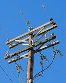 stock photo of nonrenewable  - high power electric lines closeup with blue sky - JPG