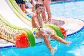 A Happy Boy On Water Slide In A Swimming Pool Having Fun During Summer Vacation In A Beautiful Aqua  poster