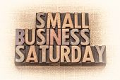 Small Business Saturday word abstract - text in vintage letterpress wood type against burlap canvas, poster