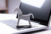 Close-up Of Trojan Horse Icon On Laptop Keypad poster