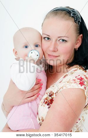 Baby With A Pacifier In The Arms Of Mother