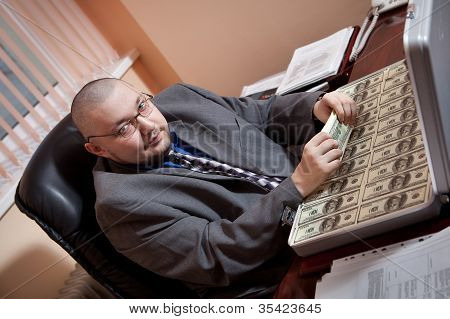 Serious Businessman With The Suitcase Full Of Dollars