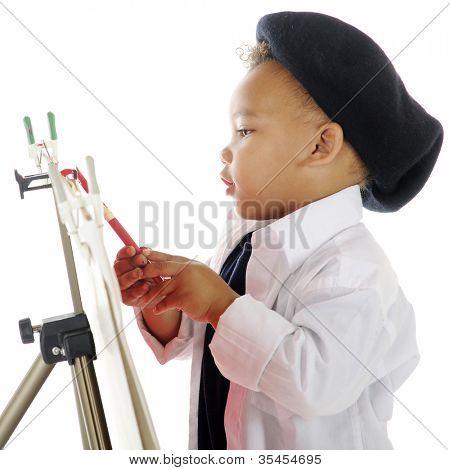 Close-up beeld van een schattig preschool kunstenaar schilderen op een ezel in zijn Kiel en Franse baret.  O
