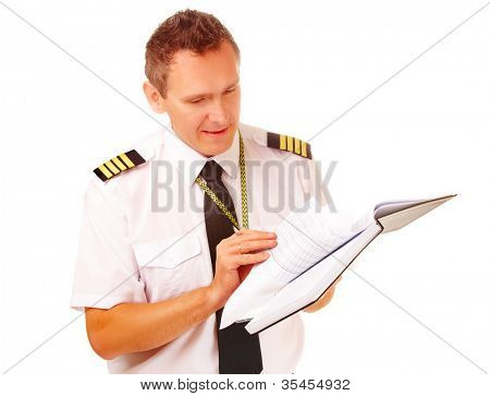 Airline pilot wearing shirt with epaulets and tie filling in and checking papers logbook, weather forecast. Headset on the table.