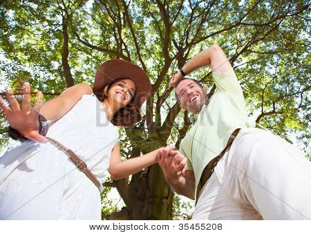 Happy young couple having fun and dancing under the tree. Summer set
