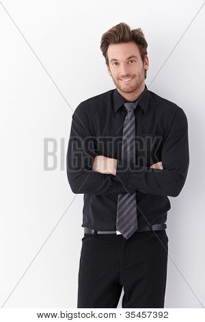 Happy young businessman standing arms crossed over white background.