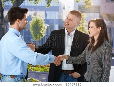 Businesspeople meeting outside of office, businessman introducing female colleague, smiling.