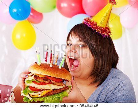 Woman eating hamburger at birthday at home.