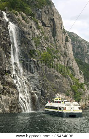 BERGEN - JUL 28: People on tour on small boat near waterfall on Pulpit Rock on Jul 28, 2011 in Bergen, Norway. 2 million tourists visit Pulpit Rock annually.