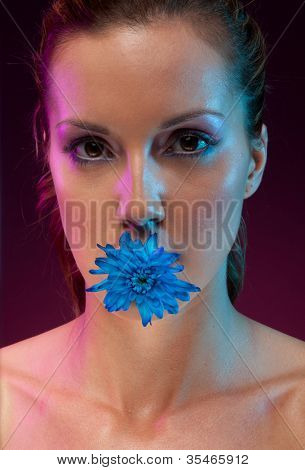 Evocative portrait of a beautiful woman with a blue flower in her mouth, studio on black