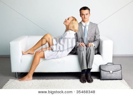 Man in business suit feeling uncomfortable setting next to a pretty lady wearing just a shirt