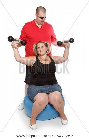 Overweight woman with her personal fitness trainer exercising with dumbbells.