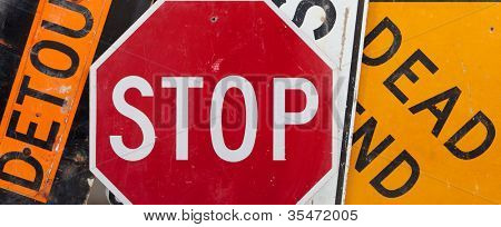 Old, vintage traffic signs including a stop sign, a detour sign, and a dead end sign making a background.  Caution theme