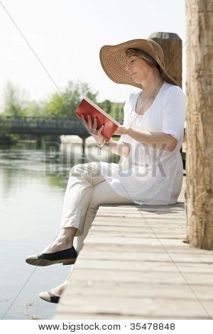 Woman realxing while reading a book by river