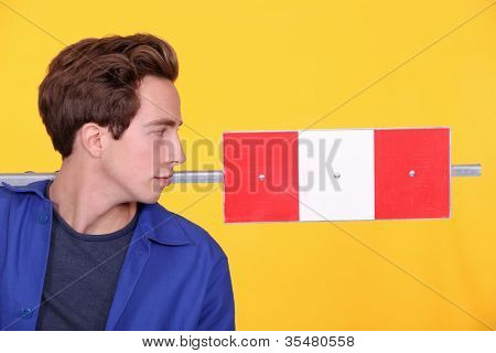 Man stood with road sign in studio