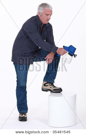Mature man using paint sprayer
