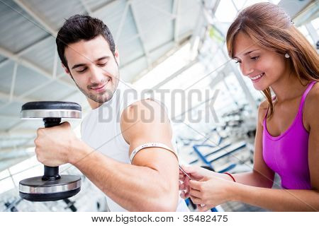 Gym man showing off muscles and woman measuring them