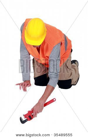 Tradesperson using a pipe wrench