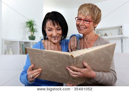 Two women looking through photo album