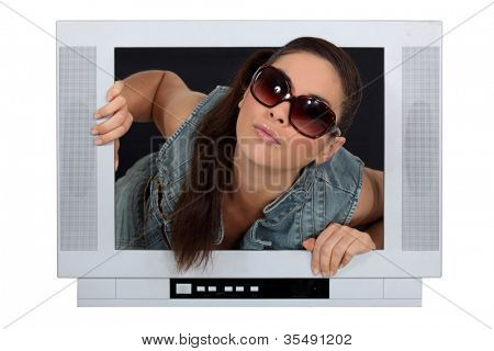 Woman coming out of a television screen