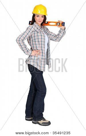 Attractive brunette holding spirit-level