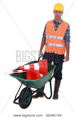 Roadworker with cones in a wheelbarrow