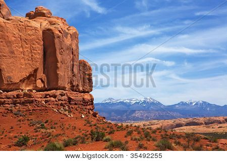 Red rock canyons and snow covered mountains with hazy blue sky