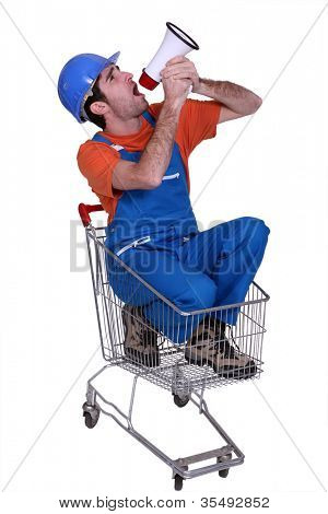 Tradesman sitting in a shopping cart and yelling into a megaphone