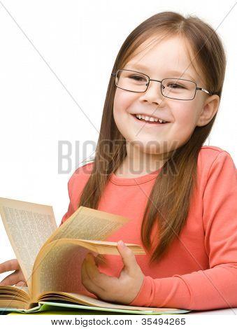 niedliche fröhlich kleine Mädchen mit Brille, isoliert über weiße Buch zu lesen