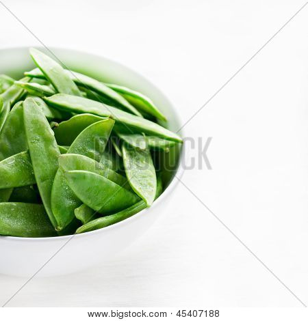 Snow peas in white bowl with copy space