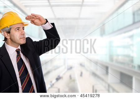 An engineer with yellow hardhat at the office