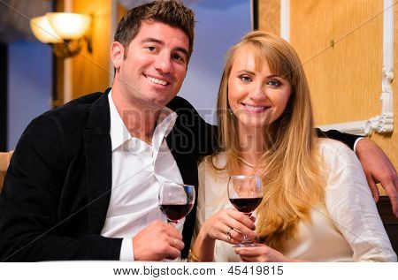 laughing embracing couple is sitting at restaurant and drinking wine