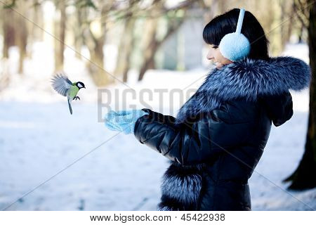 Young woman feeding birds in the winter forest