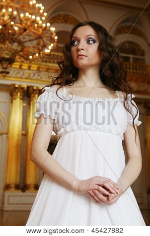 Portrait of a beautiful young victorian lady in white dress.Russian palace.