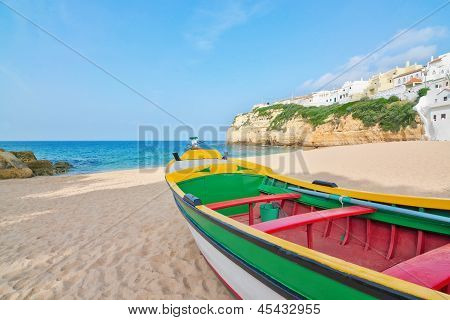 Magnificent Beach On The Coast Of Portugal At Villa Carvoeiro. Fishing Boat In The Foreground.