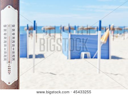 A Thermometer On The Beach In The Summer, In The Background Of Sun Beds And Umbrellas.