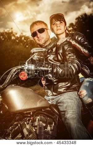 Biker couple, man and woman in leather jacket on a motorcycle.