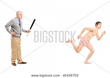 Full length portrait of an angry middle aged man with baseball bat shouting at a naked man running away, isolated on white background