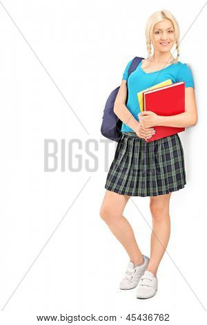 Full length portrait of a female student with school bag holding books, isolated on white background